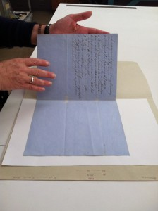 A conservator handling paper using bare hands