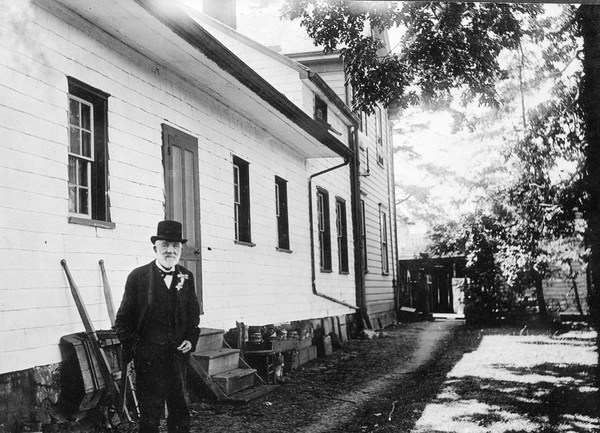 Dr. John Sebastian Helmcken in front of his Elliot Street residence in Victoria.