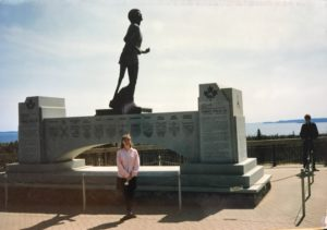 Photograph of a woman standing in front of a monument to Canadian Terry Fox.